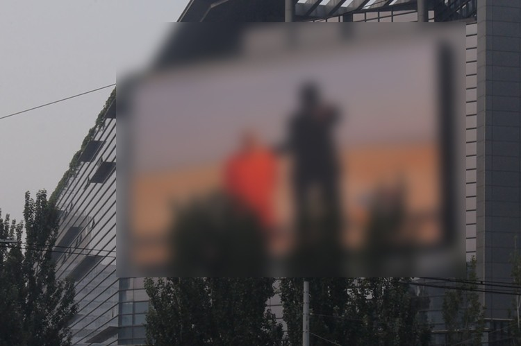 Graphic footage of executed US journalist shown on giant TV screen in heart of Beijing